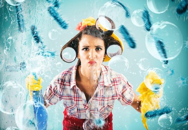Grappige huisvrouw bezig met huishoudelijke schoonmaak met sproeidesinfectiemiddel