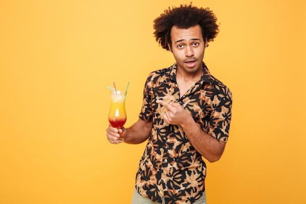 Grappige jonge afrikaanse man cocktail drinken.