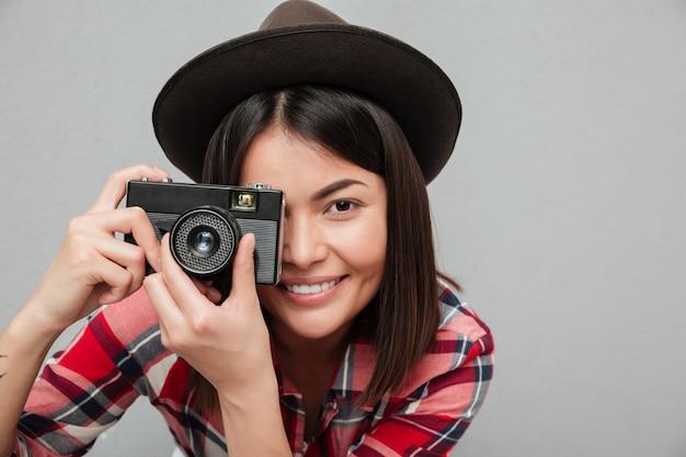 Grappige jonge aziatische vrouw die over de grijze camera van de muurholding wordt geïsoleerd.