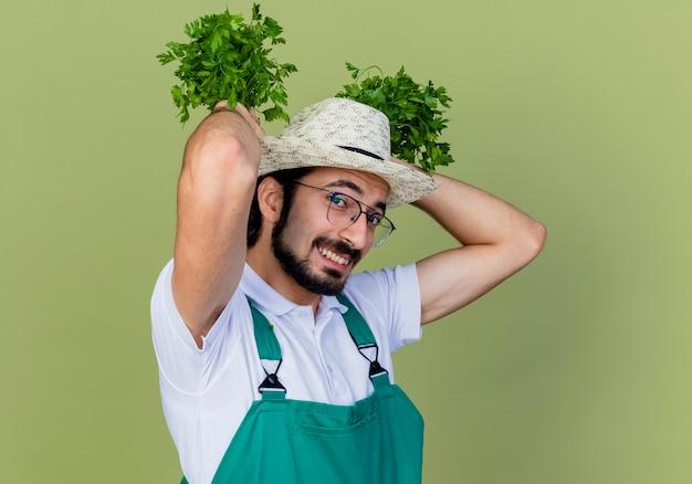 Grappige jonge bebaarde tuinman man met jumpsuit en hoed met verse kruiden kijken voorkant lachend met blij gezicht staande over lichtgroene muur