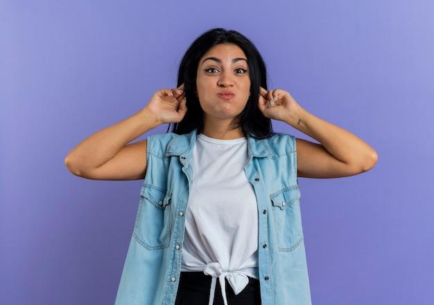 Grappige jonge blanke vrouw waait wangen en hand in hand achter de oren geïsoleerd op paarse achtergrond met kopie ruimte