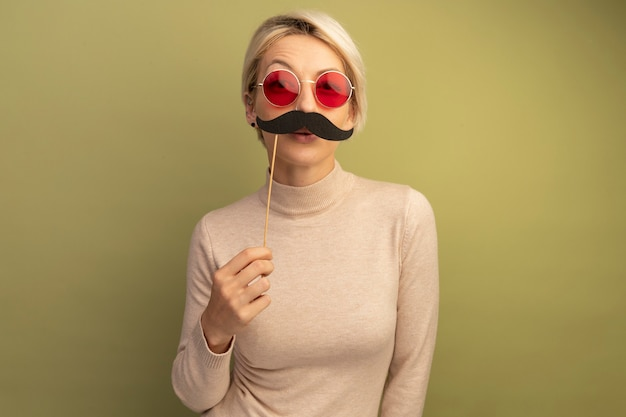 Grappige jonge blonde vrouw die een zonnebril draagt met een valse snor op een stok boven de lippen en kijkt naar de voorkant geïsoleerd op een olijfgroene muur met kopieerruimte