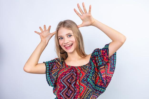 Grappige jonge blonde vrouw handen op haar hoofd zetten en hoorns gebaren met vingers