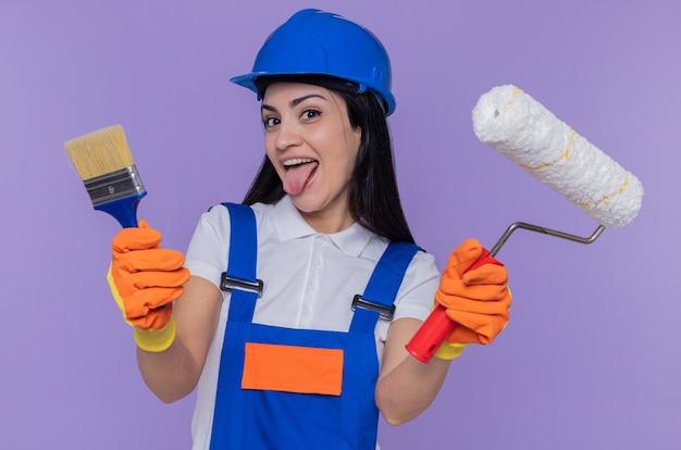 Grappige jonge bouwersvrouw in eenvormige bouw en veiligheidshelm die rubberhandschoenen dragen die verfroller en penseel houden