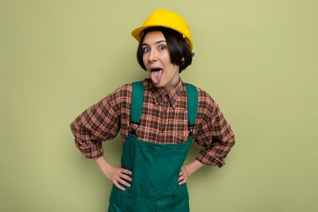 Grappige jonge bouwvrouw in bouwuniform en veiligheidshelm die tong uitsteekt die op groen staat