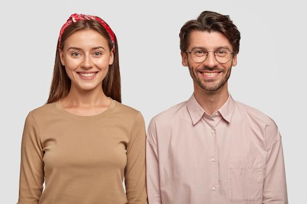 Grappige jonge collega's grinniken en glimlachen breed