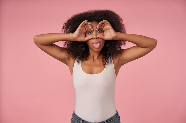 Grappige jonge donkere vrouw met krullend haar gek op roze in vrijetijdskleding, vreugdevol en tong tonen, handen opheffen naar haar ogen