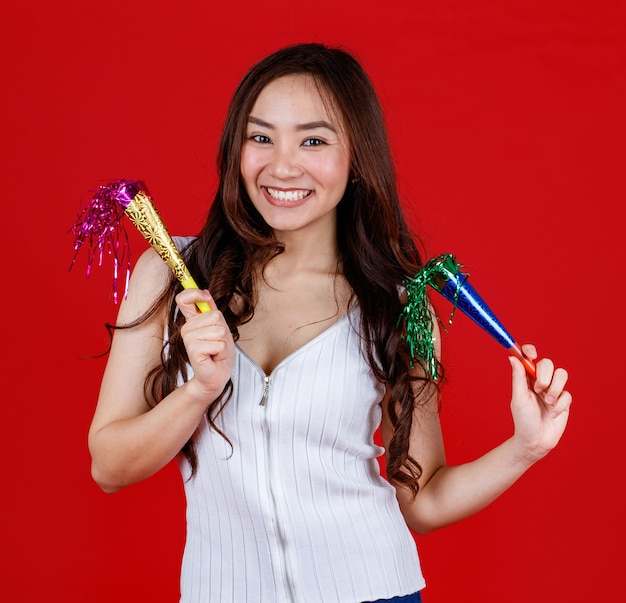 Grappige jonge en genezende aziatische meid die feestpoppers vasthoudt en speelt met grappig en gelukkig. studio opname op rode achtergrond.