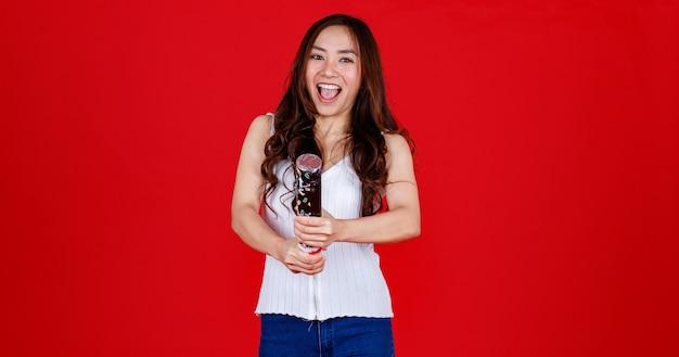 Grappige jonge en genezende aziatische meid die feestpoppers vasthoudt en uitblaast met grappig en gelukkig. studio opname op rode achtergrond.