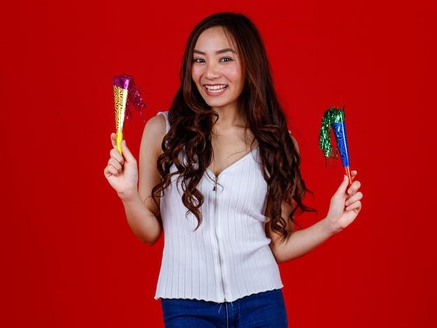 Grappige jonge en genezende aziatische meid die vasthoudt en klaar is om feestpoppers te spelen met grappig en gelukkig. studio opname op rode achtergrond.