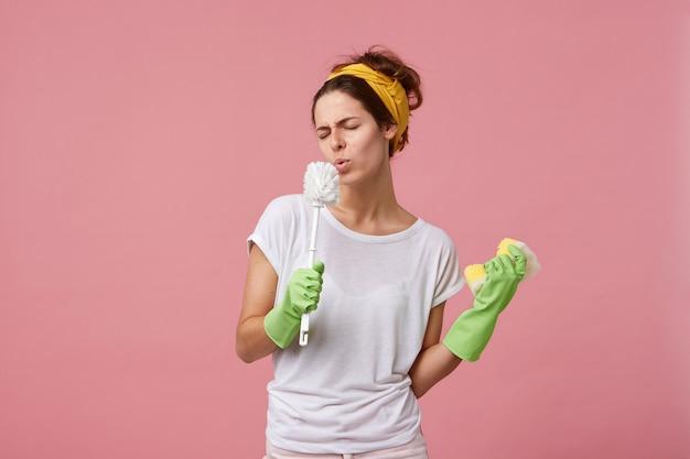 Grappige jonge europese huisvrouw dragen hoofdband, casual t-shirt en groene rubberen handschoenen genieten van schoonmaakproces thuis, spons en toiletborstel houden op haar mond als een microfoon en ondertekening