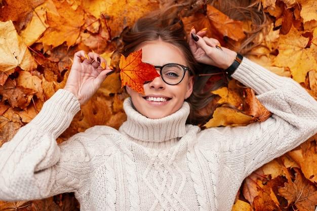 Grappige jonge hipster vrouw in een modieuze gebreide trui in stijlvolle bril met een oranje blad in handen spreekt verbazing liggend op herfstbladeren in het bos. positieve meisje model rusten.