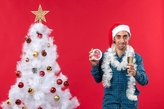 Grappige jonge kerel met de hoed van de kerstman en het verhogen van een glas wijn en het houden van klok status
