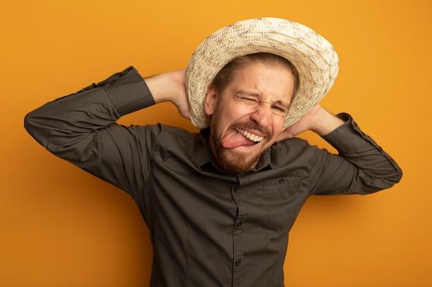 Grappige jonge knappe man in grijs shirt en zomerhoed grimas hand in hand achter zijn nek maken