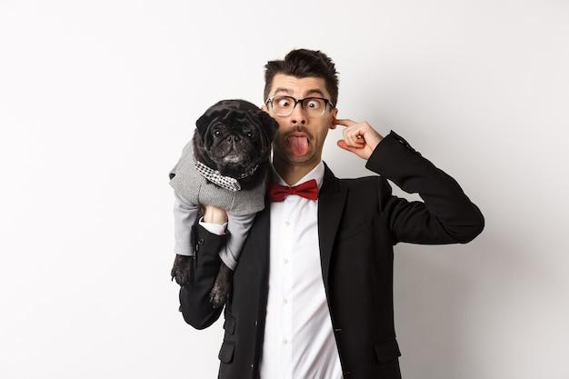 Grappige jonge man in feestpak, tong tonen en schattige zwarte pug op schouder houden, vieren met huisdier, staande op witte achtergrond.