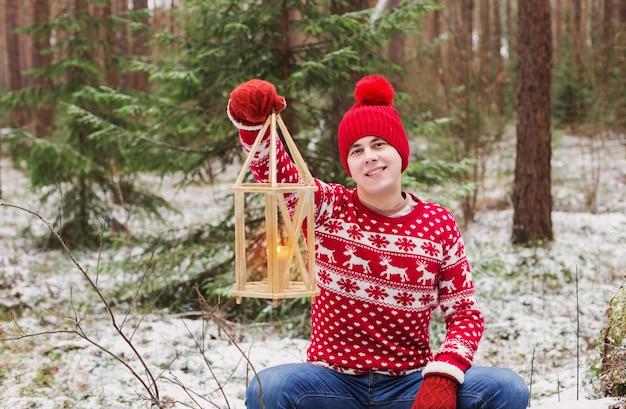 Grappige jonge man in rode hoed in winter woud