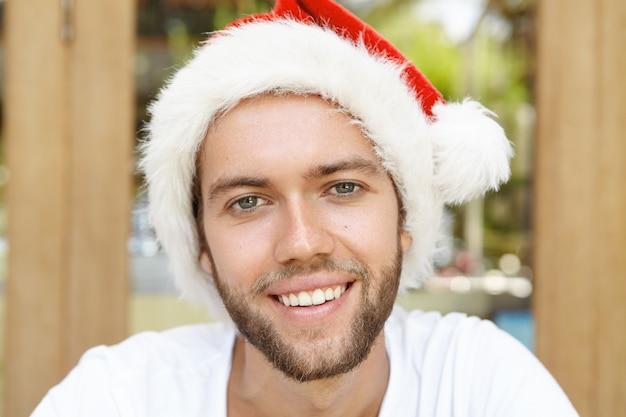 Grappige jonge man in rode hoed met witte vacht glimlachend gelukkig, genieten van vakantie in land met warm klimaat.
