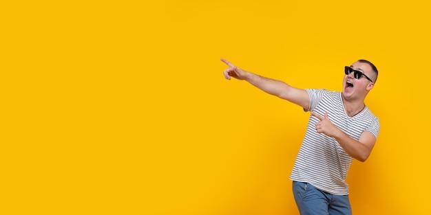 Grappige jonge man in vrijetijdskleding wijzende vingers opzij geïsoleerd op gele achtergrond