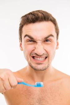Grappige jonge man met tandenborstel