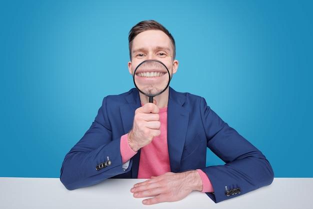 Grappige jonge man met vergrootglas door zijn brede glimlach zittend door bureau geïsoleerd