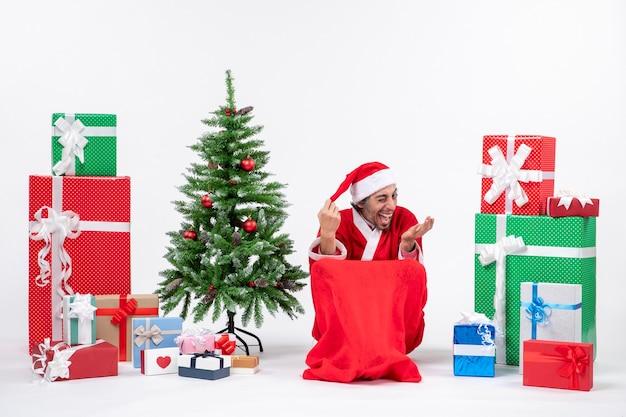 Grappige jonge man verkleed als kerstman met geschenken en versierde kerstboom op witte achtergrond