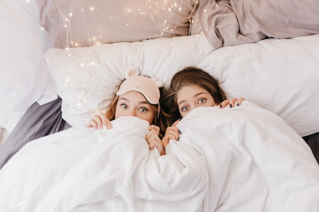 Grappige jonge meisjes verstopt onder een deken. binnenfoto van emotionele zussen die lol hebben tijdens de ochtendfotoshoot.