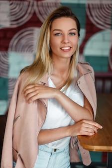 Grappige jonge modelvrouw met een glimlach in een roze jasje en denimborrels die binnenshuis op een stoel zitten