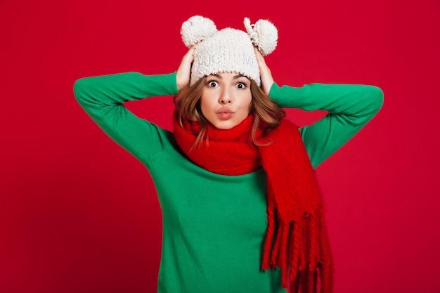 Grappige jonge mooie dame die hoed en warme sjaal draagt