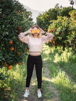 Grappige jonge mooie vrouw die zich in oranje boomgaard bevindt en twee oranje helften voor haar ogen houdt