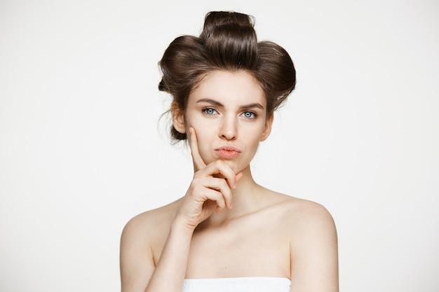 Grappige jonge mooie vrouw in haarkrulspelden en handdoek het stellen. schoonheid cosmetologie en spa.