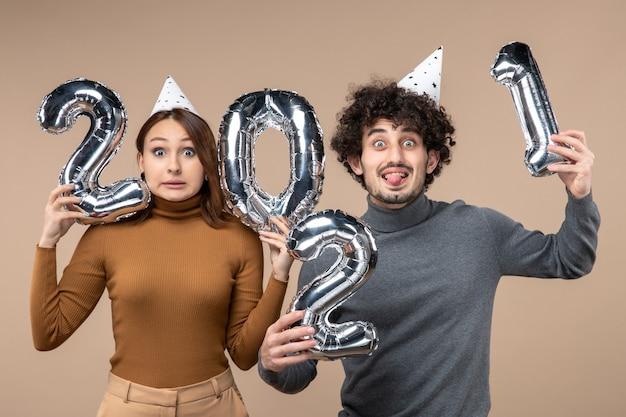Grappige jonge paar dragen nieuwe jaar hoed vormt voor camera meisje toont en en jongen