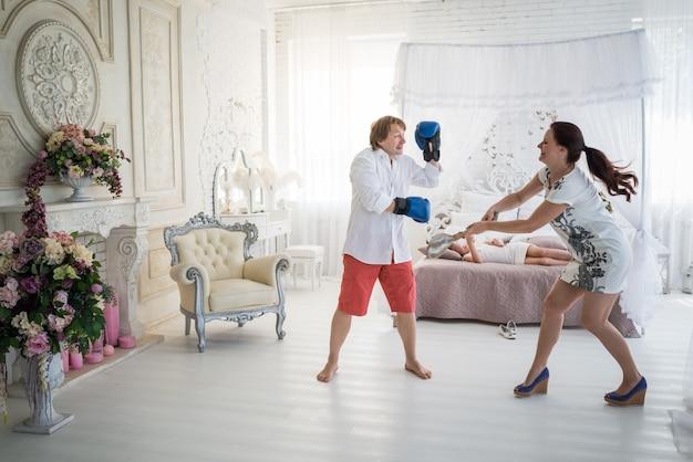 Grappige jonge paar man en vrouw vechten met bokshandschoenen tegen het oppervlak van een lachende oudere dochter liggend op het bed