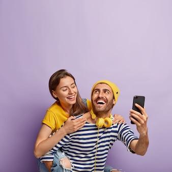 Grappige jonge paar nemen selfie op smartphone, genieten van meeliften rit, hebben gelukkige uitdrukkingen, mooie vrouw knuffels vriendje van achteren, geïsoleerd op violette achtergrond. mensen