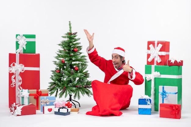 Grappige jonge volwassene verkleed als kerstman met geschenken en versierde kerstboom zittend op de grond wijzend boven perfect gebaar maken op witte achtergrond