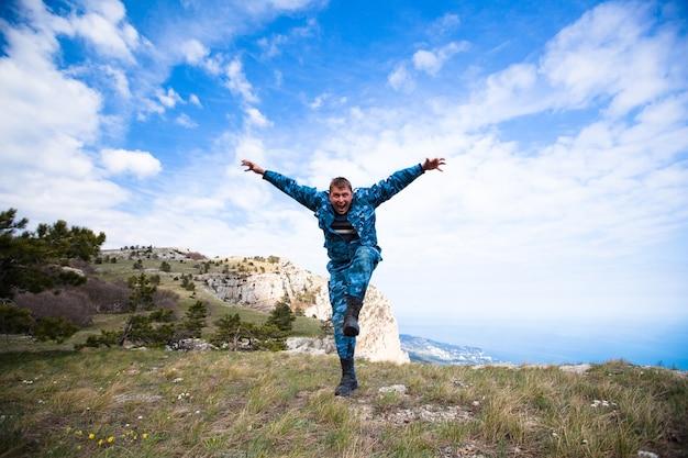 Grappige jonge vrolijke blanke man springen op de heuvels met groen gras tegen een blauwe lucht en witte wolken. concept van langverwachte reizen en toerisme