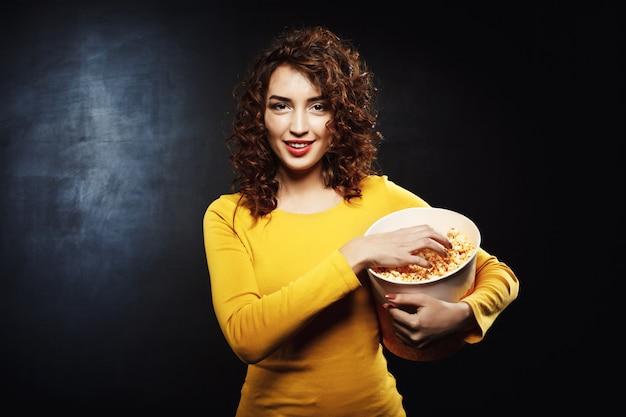 Grappige jonge vrouw die handvol popcorn met vrolijke glimlach grijpen