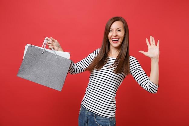 Grappige jonge vrouw die palm toont, hand zwaait, pakketten vasthoudt met aankopen na het winkelen geïsoleerd op een felrode muurachtergrond. mensen oprechte emoties, lifestyle concept. bespotten kopie ruimte.
