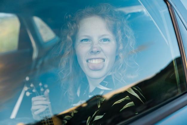 Grappige jonge vrouw die rond in auto voor de gek houden