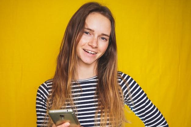 Grappige jonge vrouw in gestreept shirt en mobiel in de hand geïsoleerd over geel