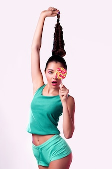 Grappige jonge vrouw in groene jumpsuitholding lolly en het stellen