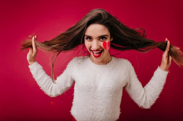 Grappige jonge vrouw in pluizige trui poseren in valentijnsdag met glimlach