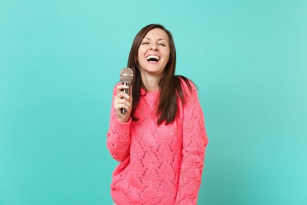 Grappige jonge vrouw lachen in gebreide roze trui in de hand houden, zingen lied in microfoon geïsoleerd op blauwe turquoise muur achtergrond, studio portret. mensen levensstijl concept. bespotten kopie ruimte.