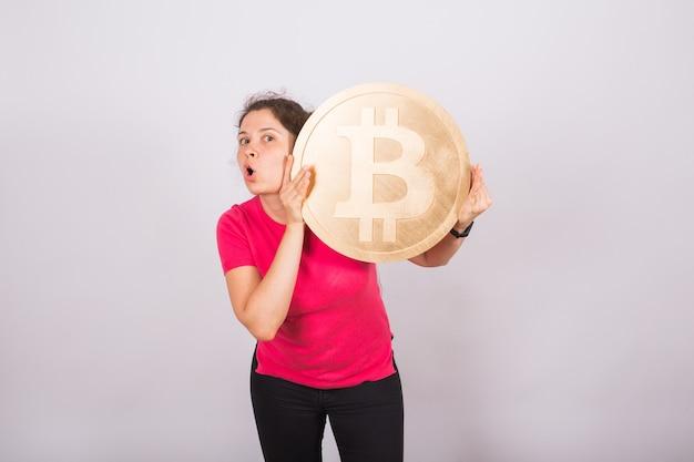 Grappige jonge vrouw met grote bitcoin op witte ruimte
