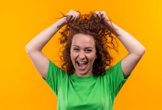 Grappige jonge vrouw met kort krullend haar in groen t-shirt camera kijken verlaten en blij haar haar aan te raken