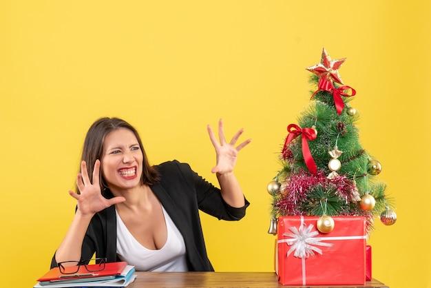Grappige jonge vrouw op zoek naar iets met verbaasde gezichtsuitdrukking zittend aan een tafel in de buurt van versierde kerstboom op kantoor op geel
