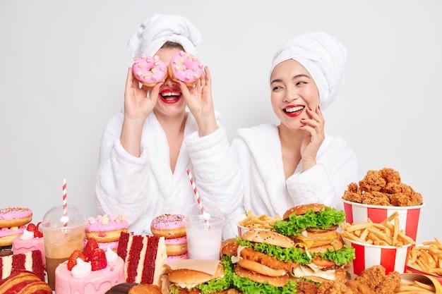 Grappige jonge vrouwen brengen vrije tijd thuis door, dwaas rond, houden heerlijke zoete donuts boven de ogen, omringd door lekker fastfood