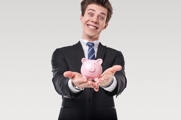 Grappige jonge zakenman in formeel pak die spaarvarken demonstreert en gelukkig glimlacht terwijl hij geldbesparende concept vertegenwoordigt op witte achtergrond