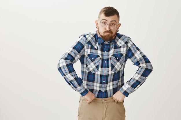 Grappige jongeman in glazen die zich gedraagt als oude grootvader