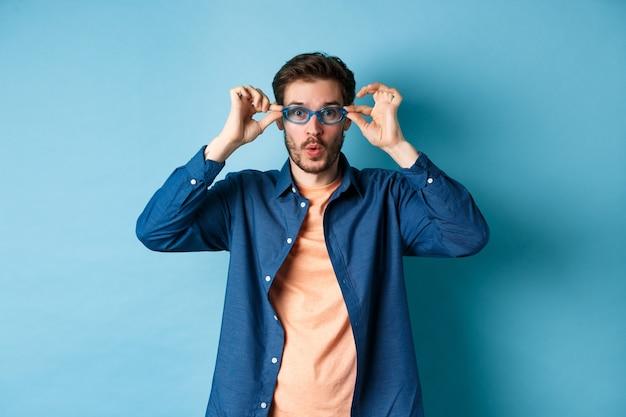 Grappige jongeman probeert nieuwe zonnebril, kijkt verrast camera, staande op blauwe achtergrond. kopieer ruimte