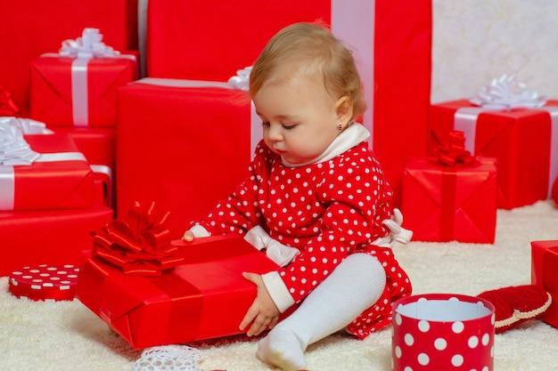 Grappige jongen baby met kerstcadeaus